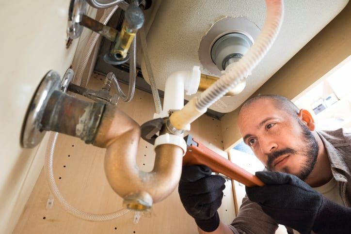 plumber working under sink